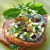 Tartines aux légumes méditerranéens Ingrédients  pour 4 personnes 100 g d'aubergine 100 g de courgette 50 g d'olives noires dénoyautées 60 g de yaourt nature 160 g de fromage de chèvre frais 6 brins de basilic 1 cuillerée à soupe d'huile d'olive 1 pain d'épeautre