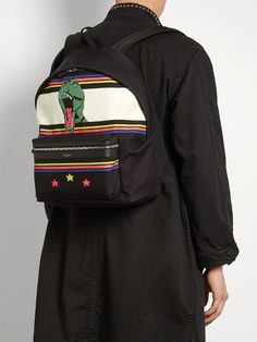 This black canvas City backpack reflects Saint Laurent's innately cool aesthetic. It's made in Italy with an eye-catching dinosaur print with blue, pink and neon-green stripes and stars, and is finished with slick tonal leather trims for subtle structure. Rely on the adjustable padded shoulder straps for optimum comfort on busy city days.