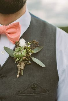 A loose succulent boutonniere with cotton and greenery, created by Elaine Pisarcik.