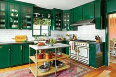 The homeowner replaced the lower cabinets and gave the uppers new life with glass doors and brass hardware. Tired of white kitchens, she drenched the entire space in a custom deep, dark green in a glossy lacquered finish. Her collection of white dishes and serving pieces, an impressive La Cornue range, and a white subway-tile backsplash add interest and break up the swaths of green.  See more of this Before and After: Redo with Color!