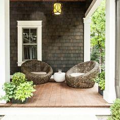 Beautiful covered porch. I love the dark shingled siding.