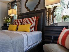 Modern style mixes with mountain architecture in this master bedroom, and the result is a comfy room with lots of personality, bright colors and sleek twists on classic rustic style.