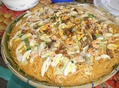 Pancit palabok (rice noodles with shrimp sauce topped with shrimp, boiled egg, green onions, smoked fist, etc.
