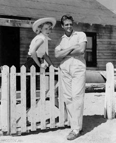 Full BTS shot of Anne Francis as Liz Worth and John Ericson as Pete Wirth, standing by white picket fence.
