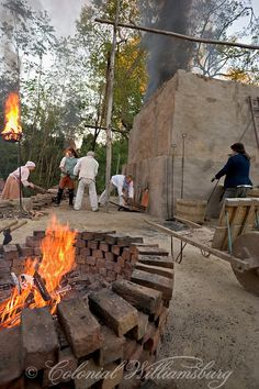 Brickmakers feed the fires of the brick kiln with wood.  Historic trades at Colonial Williamsburg, Williamsburg, Virginia