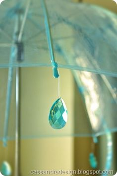 "Umbrella with ""raindrop"" prisms hanging over a party table  http://cassandradesign.blogspot.com/2012/04/april-showers-bringbirthday-sisters.html  #umbrella #centerpiece #rain #drops #raindrop #prism #party #ideas"