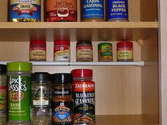 use a tension rod to utilize vertical space in a cupboard to hold smaller spice containers...