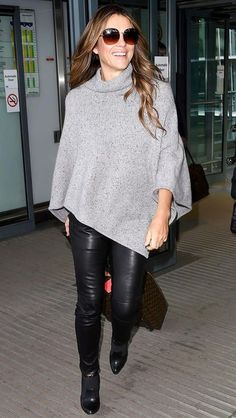 Elizabeth Hurley in black leather leggings, booties and a gray sweater poncho... - Celebrity Street Style
