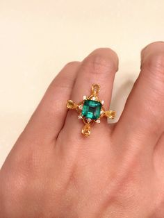 Emerald , yellow sapphire and diamonds ring , the contrasting color stones are set in 18k yellow gold , elegant design .