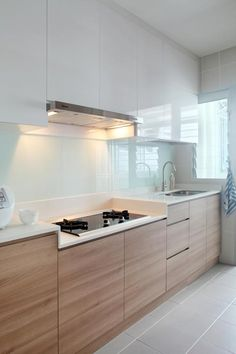 This 4 room HDB kitchen is in line with the clean and understated concept of the living and dining area. White cabinets line the walls, complemented with light grey tiles and a glass wall (back splash) behind the sink.