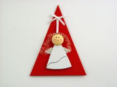 Christmas Angel - A beautiful and versatile folded triangle card made from the highest quality coloured card. Its pure solid colour flows through its surface which features a crisp, original smooth finish. Design features a plywood angel, which can be used to decorate your own Christmas tree. It comes with red envelope in protective cellobag.