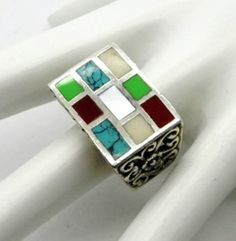 This is a Bold Vintage Turquoise, Coral and MOP Inlaid in a Square Face Sterling Silver Ring with scrollwork on each side of the band  The ring