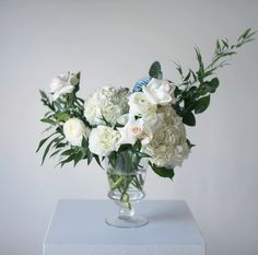 Green and white wedding ceremony pedestal arrangement with white hydrangea, white roses, white ranunculus, italian ruscus and eucalyptus in a clear glass pedestal vase