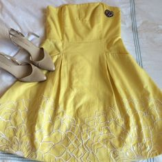 Lilly Pulitzer strapless yellow cotton dress This is a must have!! Flattering form fitting top with slotted pockets. It has beautiful white embroidered flowers along the bottom. In flawless condition. 30 inches long. Lilly Pulitzer Dresses Strapless