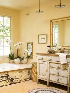 architectural salvaged tin on the tub, woven hamper, chippy dresser turned vanity.