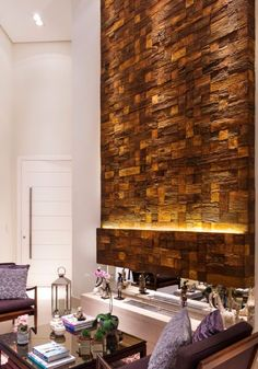 This contemporary living room has a concrete wall panelling that resembles natural wood. There is a variety of designs available including ones that resemble wood, natural stone and ones that are geometric shapes.