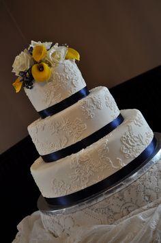 Simple white cake. Blue ribbon. Yellow flower
