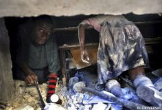 """Un hombre intenta rescatar a una profesora atrapada bajo los escombros de un colegio ante el cadáver de una niña (d) que murió durante el terremoto de Haití en enero de 2010. La foto es parte de una serie de tomas sobre la catástrofe ocurrida en Haití por un terremoto en 2010. Fueron tomadas por Carol Guzy, Nikki Kahn y Ricky Carioti, de The Washington Post. Los profesionales recibieron el premio Pulitzer en la categoría """"Fotografía de Última Hora"""""""