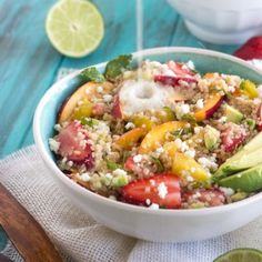 A white bowl filled with quinoa salad filled with different fruits and dressing being poured on top
