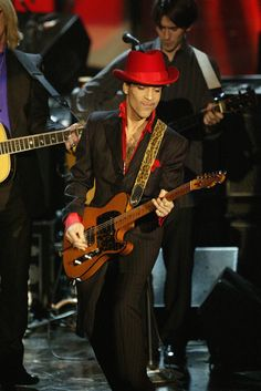 """Prince was honored in 2004 with induction into the Rock and Roll Hall of Fame.  Here, Prince performs solo on """"While My Guitar Gently Weeps"""" following George Harrison's induction at the Rock & Roll Hall of Fame 19th Annual Induction Dinner at the Waldorf Astoria Hotel on March 15, 2004 in New York City. (Tom Petty and Dhani Harrison in the back)  Credit: Frank Micelotta/Getty Images"""