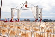 Love the view from this mandap with gold tulle wrap on the chairs