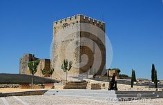 Photo taken inside the fortress of Motta to Estejo-Alcala la Real in Spain. The picture shows, in the foreground, an old cannon, behind which we see the big and still in good condition great crenellated tower with a square base that stands out in the blue sky.