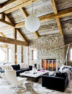 Why It Works: Double Sofas // chalet, cabin, black sofa, fireplace, stone wall, pendant light, side chair