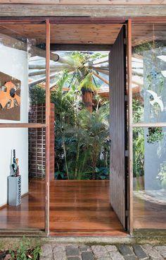 A porta da entrada principal abre-se para o jardim interno. Ao redor dela, esquadrias de madeira e vidro garantem o interior iluminado, embora a casa esteja no meio de uma mata fechada.