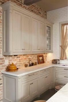 Gray Kitchen Cabinet against Brick Backsplash and White Honed Carrara Countertop