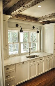 Kitchen with white cabinets, gray marble countertops, wooden beams, hardwood floors.