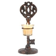 """Crafted of cast iron in an ornate skeleton key silhouette, this candleholder adds a stately touch to your mantel or sideboard. Product: CandleholderConstruction Material: Iron and glassColor: Rust and amber  Features: Key silhouette Accommodates: (1) Votive candle - not includedDimensions: 11.5"""" H x 4.5"""" Diameter"""