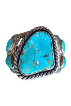 """~ Heavy Vintage Navajo Turquoise Cuff, $595.00.  This is incredible, heirloom Navajo cuff is circa 1980.  Asymmetricalcenter stone from the Cripple Creek mine shows some crazingand is encircled with traditionalrope-style silver-work. Four additional stones flank the center stone.  Size: 2"""" x 5"""" x 1"""" Weight: 110 grams Marks: RG, sterling Condition:minor crazing to main stone - see image, good vintage condition Available from DDR. ~"""