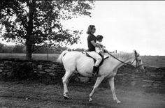 First lady Jacqueline Kennedy holds her son John F. Kennedy Jr. as she rides towards her familys home at Hammersmith Farm, where she is spending her vacation, on September 12, 1962, near Newport, Rhode Island