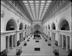 Stanley Field Hall from balcony. Overview of exhibit cases, Roman bronzes including bathtub, elephants, looking south towards Chinese Gateway under stairway. Field Museum of Natural History interior. 1922.