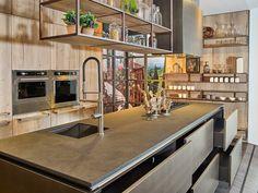 Wat een uitstraling heeft deze keuken! Het materiaal van het kookeiland en de keukenlades is echt te gek! Tel daarbij op het stoere hout tegen de wanden en het gave hangende element boven het kookeiland en deze keuken is helemaal compleet!