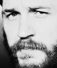 Tom Hardy bearded in black and white looking sort of surly.