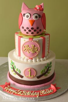 "Look ""Hoo's"" One #1Milestones This two tier cake is iced in ivory buttercream & trimmed with a beaded border on one tier & brown/pink fondant on the second tier.. The owl topper is handmade with gum paste. A personalized name plate adds a neat touch!"