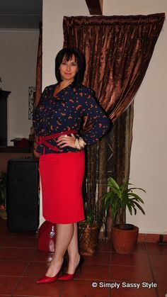 Red pencil skirt topped with a navy shirt that has a pretty floral print to it, red ombre pumps and a knotted belt - professional administrative assistant look