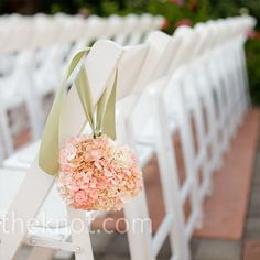Small pink pomander balls on aisle seats at the ceremony.