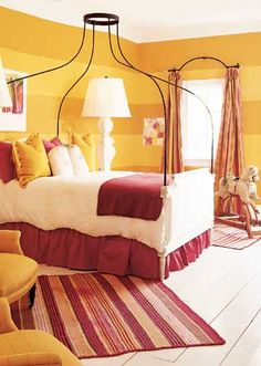 Striped with Style  Wide horizontal stripes in two tones of orangey-gold encircled this space with a contemporary element. Arched iron curtain rods and canopy bed draw the eye up, while bold red rugs and bed skirt ground the furnishing to a pale floor.