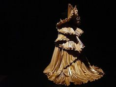This baroque angel of gold pleated dress is his vision of an angel ascending to heaven.  Roberto saw the joy in living and wanted to imbue that in his work.
