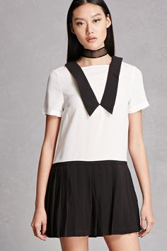 This woven mini dress features a boxy silhouette with a contrast pleated skirt, contrast plunging collar overlay, short sleeves, and a concealed back zipper. This is an independent brand and not a Forever 21 branded item.