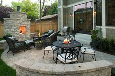 outdoor patio with fireplace and curved wall bench
