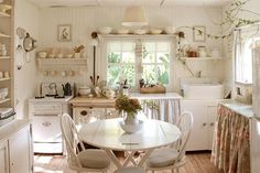 Sweet white small-ish kitchen, skirted cabinets, open shelving, farmhouse sink, smaller than usual stove.