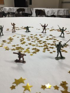 Party on a budget Army themed going away party. Center pieces with gold star confetti and Soldier toys.