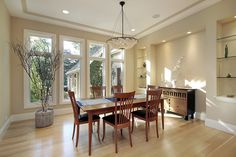 Contemporary home with bright dining room in off-white color scheme.  Dining furniture is wood and the light interior design continued with light wood flooring.