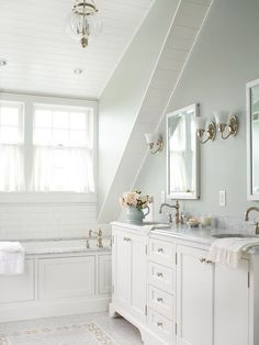 White Slanted Ceiling  Use a white palette to showcase architectural gems, such as this bathroom's beaded-board slanted ceiling. White cupboards, trim, and ceiling paint carry light through the space, while brass fixtures and a mosaic stone tile floor set the room aglow.