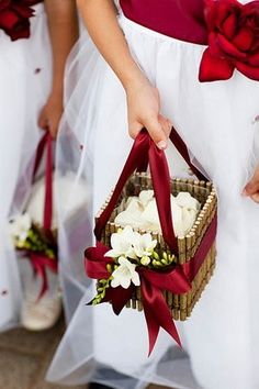 Love these basket for a winter wedding  snowy white roses and rich red ribbons - perfection!  This as a wedding bouqeut with a plant in iot instead of cut flowers