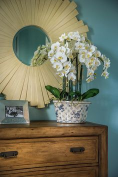 Bedroom Decor Ideas A rosette mirror complements the blue walls, emphasizes warmth from the wooden chest and highlights yellow accents in the floral arrangement. #BedroomDecor