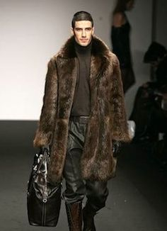 Male runway model wearing brown mink coat.